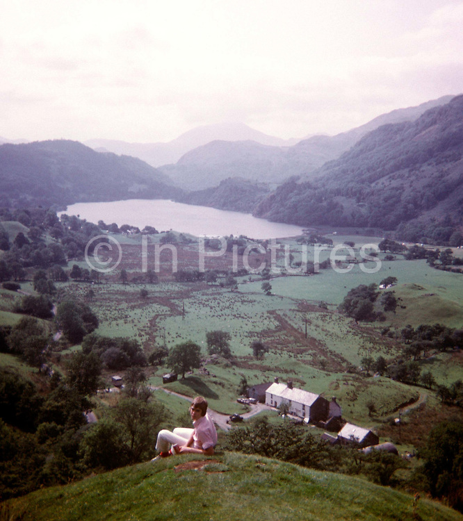 A portrait of a teenage boy of about 16 years-old with Welsh mountains and hills in the background in the 1970s. With a rolling valley, a lake, a farmhouse and misty hills in the distance, the landscape is a peaceful scene of an otherwise wild countryside in north Wales. The boy and his family are on a daytrip to the Welsh hills. It was taken on a film camera by the youth's father, an amateur photographer in 1973. The picture shows us a memory of nostalgia in an era from the last century.