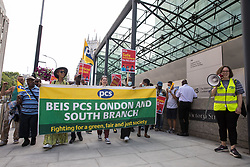 London, UK. 20th July, 2021. Members of the PCS trade union working for the outsourced contractor ISS march around their workplace at the Department for Business, Energy and Industrial Strategy (BEIS) on the second day of a 3-day strike. The striking cleaners, security guards and other support staff at the government department are demanding an end to low pay, improved working conditions, bonuses for having worked through lockdown, annual leave from last year and a Covid return-to-work protocol.