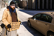 """16 FEBRUARY 2021 - DES MOINES, IOWA: A man panhandles on a street corner in downtown Des Moines. Iowa, like much of the United States, is in the grip of a frigid Polar Vortex. Temperatures in Iowa have been 30F below normal for more than a week. Tuesday morning, 15 February, was the coldest morning so far and is expected to be the coldest morning in central Iowa this winter. The temperature in Des Moines was -17F (-27C), with the windchill factored in the """"feels like"""" temperature was -25F  (-32C). Schools have been closed for the last two days so students wouldn't have to stand outside waiting for buses. Most outdoor activities, like outdoor construction and road work, are paused until temperatures rebound. The public libraries, closed because of the Coronavirus pandemic, were opened as warming centers, and the city buses were free so people could ride the buses to stay warm.       PHOTO BY JACK KURTZ"""