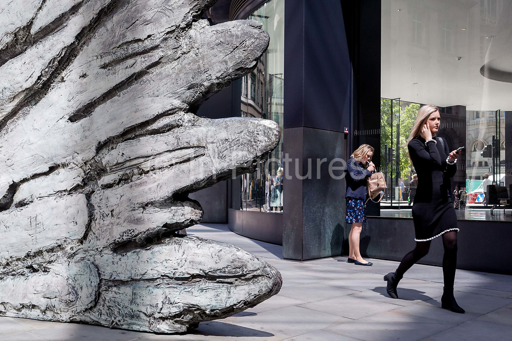 A lady lights a cigarette as a younger, healthier woman walks past the sculpture entitled City Wing on Threadneedle Street in the City of London, the capitals financial district, on 17th June 2019, in London, England. This ten-metre-tall bronze sculpture is by President of the Royal Academy of Arts, Christopher Le Brun, commissioned by Hammerson in 2009. 'The City Wing' and has been cast by Morris Singer Art Founders, reputedly the oldest fine art foundry in the world.