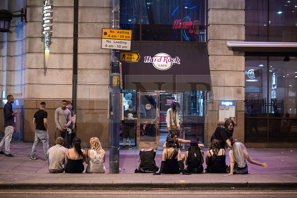 © Licensed to London News Pictures . 15/06/2014 . Manchester , UK . People sit on the pavement in front of Hard Rock cafe . People on a night out in Manchester City Centre overnight , following England's defeat to Italy in the World Cup . Photo credit : Joel Goodman/LNP