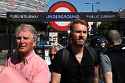 People exit Notting Hill Gate underground station to visit Portobello Road Market in Notting Hill, West London, England, United Kingdom. People enjoying a sunny day out hanging out at the famous Sunday market, when the antique stalls line the street.  Portobello Market is the worlds largest antiques market with over 1,000 dealers selling every kind of antique and collectible. Visitors flock from all over the world to walk along one of Londons best loved streets.