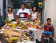 (MODEL RELEASED IMAGE). In a rare moment, when not surrounded by the in-laws and cousins with whom they share a Colonial-era house, the Costa family: Ramon Costa Allouis, Sandra Raymond Mundi, and their children Lisandra, and Fabio, in the courtyard of their extended family's home in Havana, Cuba with one week's worth of food. The Costa family is one of the thirty families featured in the book Hungry Planet: What the World Eats (p. 96)