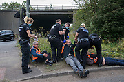 Police officers arrest Insulate Britain climate activists who had been blocking a slip road from the M25, causing a long tailback on the motorway, as part of a new campaign intended to push the UK government to make significant legislative change to start lowering emissions on 13th September 2021 in Godstone, United Kingdom. The activists, who wrote to Prime Minister Boris Johnson on 13th August, are demanding that the government immediately promises both to fully fund and ensure the insulation of all social housing in Britain by 2025 and to produce within four months a legally binding national plan to fully fund and ensure the full low-energy and low-carbon whole-house retrofit, with no externalised costs, of all homes in Britain by 2030 as part of a just transition to full decarbonisation of all parts of society and the economy.
