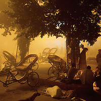Rickshaw riders gather around a fire beneath streetlighting in the dawn chill of Moradabad railway station...Moradabad,.Uttar Pradesh, India..November 2006.
