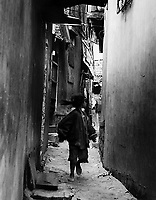 Young vietnamese girl looking back as she runs down an alleyway in village near Nha Trang harbour, Vietnam.