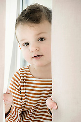 Portrait of boy playing with curtain