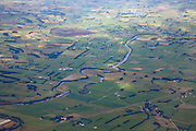 Aerial view over green pastures and farmland in Southland, New Zealand