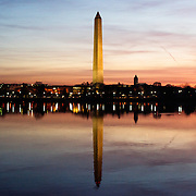 The Washington Monument, standing at the heart of the National Mall, is reflected on the predawn still waters of the nearby Tidal Basin in Washington DC.