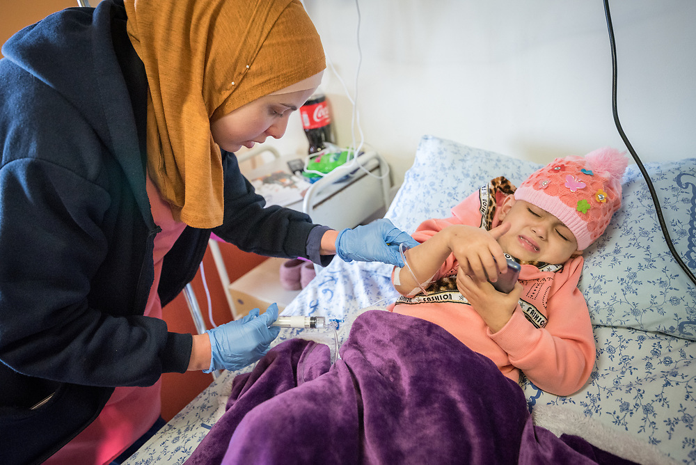 24 February 2020, Jerusalem: Four-year-old Lana, from Gaza, is tended to by one of the nurses at the Augusta Victoria Hospital in Jerusalem. With the support of the Lutheran World Federation, Lana has come to the hospital to spend a full month there, in order to go through radiotherapy treatment for a brain tumor.