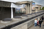 "A contractor hangs from the roof to position a banner for a new exhibition of the artist Kader Attia, of the Hayward Gallery on the Southbank, on 7th May 2019, in London, England. Kadar Attia works, ""In sculptures, installations, collages, videos and photographs that move 'back and forth between politics and poetry', Attia inventively explores the ways in which colonialism continues to shape how Western societies."""