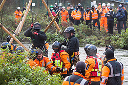 Denham, UK. 8th December, 2020. Hampshire Police officers remove Dan Hooper, widely known as Swampy during the 1990s, from the river Colne for arrest. The climate and roads activist had occupied a bamboo tripod the previous day in order to delay the building of a bridge as part of works for the controversial HS2 high-speed rail link and a large security operation involving officers from at least three police forces, the National Eviction Team and HS2 security guards was put in place to facilitate his removal.