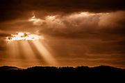 Rays of sunlight burst through a burnt orange sunset on the East Coast of Australia