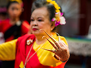 "03 APRIL 2016 - CHIANG MAI, THAILAND: A Thai woman performs a traditional northern Thai dance at the dedication of the ubosot, or ordination hall, at Wat Sri Suphan. Wat Sri Suphan is also known as the ""Silver Temple"" because of its silver ubosot, or ordination hall. The temple is more than 500 years old but the silver ordination hall was recently remodeled. The ordination hall is covered in silver and the interior is completely done in silver and gold. It's traditionally served as the main temple for the silversmiths of Chiang Mai, whose community is around the temple.     PHOTO BY JACK KURTZ"