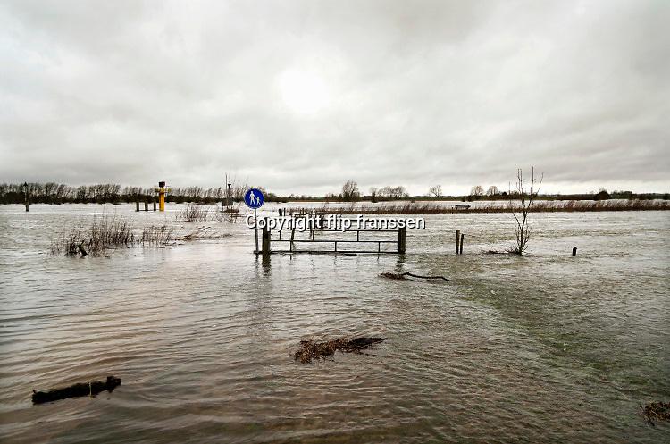 Nederland, Olst, 8-3-2020De camperplaats en loswal van dit dorp aan de IJssel staan onder water als gevolg van de hoge waterstand in de rivier. Dagjesmensen kunnen met laarzen aan nog naar de boom die op een verhoging staat . Foto: Flip Franssen