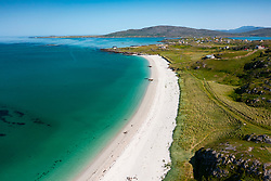 Aerial view from drone of white sand beach on Sound of Barra and village of Balla on island of Eriskay in the Outer Hebrides, Scotland, UK