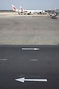 Two painted arrows stencilled on the apron of Colombo airport point in opposite directions