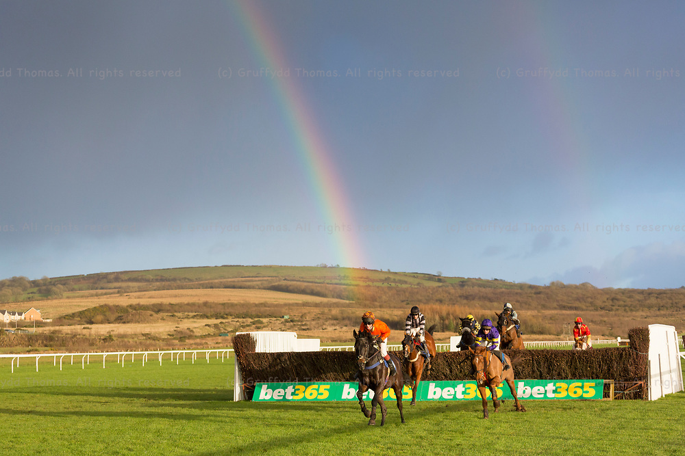 Ffos Las, Trimsaran, Carmarthenshire, Wales, UK. Sunday 12th November 2017. Spock (ridden by L Brooke) leads in the Victorian Sliders Handicap Chase as a rainbow appears behind