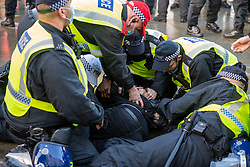 © Licensed to London News Pictures. 19/12/2020. London, UK. Police hold a man on the ground as he is arrested for allegedly being in possession of a knife in Piccadilly Circus. Protesters have gathered in central London for an anti-lockdown demonstration. Photo credit: Peter Manning/LNP