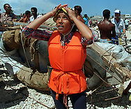 8/1994-Al Diaz/Miami Herald--In 1994 Cuban balseros turned the tiny fishing village of Cojimar into a major point of embarkation for thousands seeking a better life. Here, Gladys Garcés, 42, prays for a safe journey as she prepared to embark on the treacherous voyage 90 miles across the Florida Straits. Her life preserver, she hoped, would protect her from drowning, as well as repel sharks.