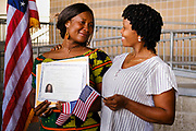 17 SEPTEMBER 2020 - DES MOINES, IOWA: NUNEE SIAH TARLEY, left, holds her naturalization certificate as she and a friend pose for pictures next to the American flag after a naturalization ceremony at Principal Park, a minor league baseball stadium in downtown Des Moines. About 75 people from 32 countries were naturalized as US citizens Thursday. It was the last citizenship ceremony in Des Moines before citizenship fees dramatically increase. Starting Oct. 2, the fee to apply for U.S. citizenship will increase from $640 to $1,160 if filed online, or $ 1,170 in paper filing, a more than 80% increase in cost. Advocates for immigration are afraid the new fees will be too expensive for many immigrants and say it's an effort by the Trump Administration to limit the number of new citizens welcomed into the United States. Because of the COVID-19 pandemic, there has been dramatic slow down in the number of naturalization ceremonies this year.          PHOTO BY JACK KURTZ