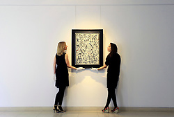 © Licensed to London News Pictures 10/04/2013.Christie's employees straighten the Jackson Pollock painting ' Number 19', estimated between $25 - $35 million, that is on display at Christie's in central London and due to go on auction for the first time in 20 years, on the 15th May in New York. .London, UK.Photo credit: Anna Branthwaite