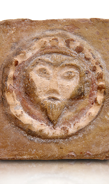 Detail of a 6th-7th Century Eastern Roman Byzantine  Christian Terracotta tiles depicting Christ - Produced in Byzacena -  present day Tunisia. <br /> <br /> These early Christian terracotta tiles were mass produced thanks to moulds. Their quadrangular, square or rectangular shape as well as the standardised sizes in use in the different regions were determined by their architectonic function and were designed to facilitate their assembly according to various combinations to decorate large flat surfaces of walls or ceilings. <br /> <br /> Byzacena stood out for its use of biblical and hagiographic themes and a richer variety of animals, birds and roses. Some deer and lions were obviously inspired from Zeugitana prototypes attesting to the pre-existence of this province's production with respect to that of Byzacena. The rules governing this art are similar to those that applied to late Roman and Christian art with, in the case of Byzacena, an obvious popular connotation. Its distinguishing features are flatness, a predilection for symmetrical compositions, frontal and lateral representations, the absence of tridimensional attitudes and the naivety of some details (large eyes, pointed chins). Mass production enabled this type of decoration to be widely used at little cost and it played a role as ideograms and for teaching catechism through pictures. Painting, now often faded, enhanced motifs in relief or enriched them with additional details to break their repetitive monotony.<br /> <br /> The Bardo National Museum Tunis, Tunisia.  Against a white background.