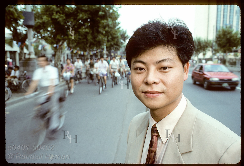 Monsanto rep Sam Chi poses outside office on Nanjing Road amid bikes & cars in central Shanghai China