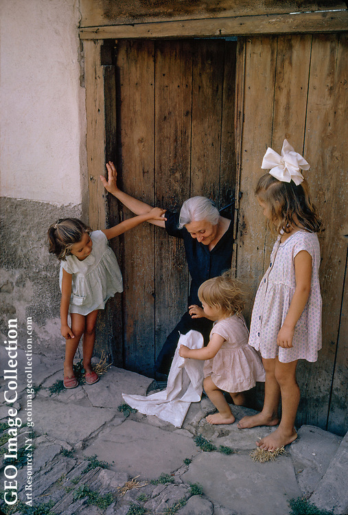 Old woman and three young girls in a doorway.