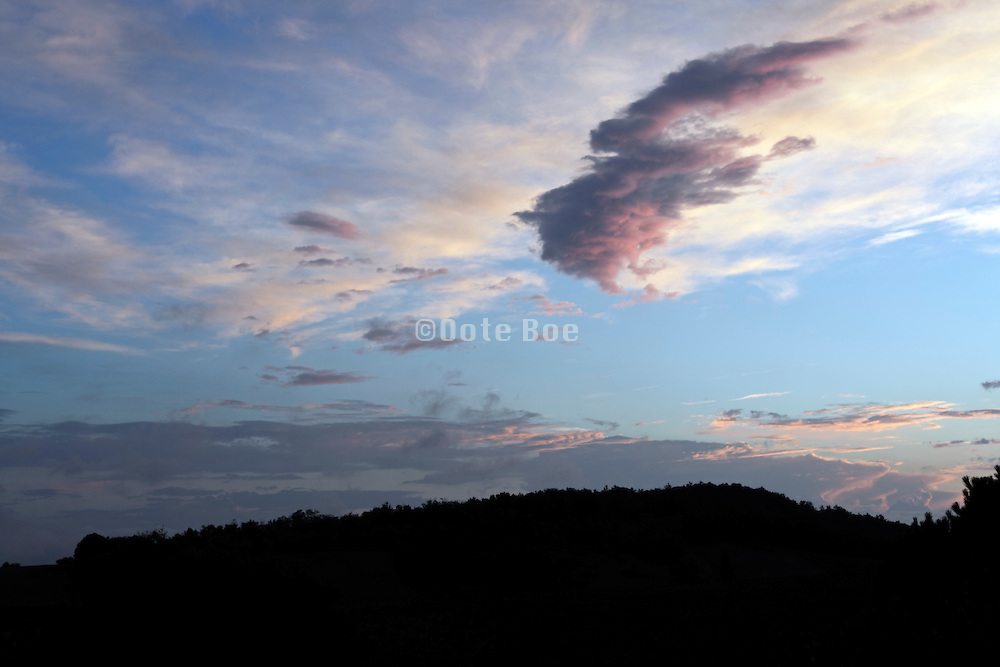 colorful sunset with clouds and hill