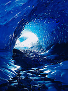 Eerie blue glow inside ice cave hollowed through stagnant ice remnant of the Muir Glacier, Glacier Bay National Park, Alaska.