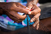 30 APRIL 2013 - MAHACHAI, SAMUT SAKHON, THAILAND:    A Burmese worker repairs a fishing net in the port of Mahachai, Samut Sakhon province, Thailand. The Thai fishing industry is heavily reliant on Burmese and Cambodian migrants. Burmese migrants crew many of the fishing boats that sail out of Samut Sakhon and staff many of the fish processing plants in Samut Sakhon, about 45 miles south of Bangkok. Migrants pay as much $700 (US) each to be smuggled from the Burmese border to Samut Sakhon for jobs that pay less than $5.00 (US) per day. There have also been reports that some Burmese workers are abused and held in slavery like conditions in the Thai fishing industry.        PHOTO BY JACK KURTZ