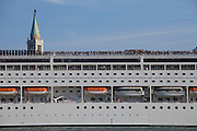 Cruise ship MSC Armonia passing through Venice in front of San Giorgio Maggiore, while its passengers enjoy a panoramic view of St. Mark's Square from the roof.