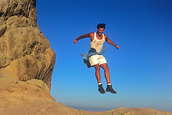 man enjoying being in midair after jumping from a rock formation in California