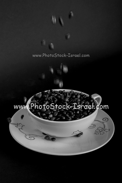 concept showing coffee beans being poured into a white coffee cup and saucer on black background