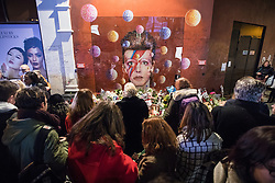 © Licensed to London News Pictures. 10/01/2017. London, UK. Fans gather around the mural of David Bowie in Brixton, south London, to commemorate the first anniversary of the star's death. Photo credit: Rob Pinney/LNP