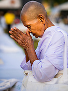 05 DECEMBER 2014 - BANGKOK, THAILAND: A Thai woman bows in prayer during a Buddhist prayer service for Bhumibol Adulyadej, the King of Thailand. Thais marked the 87th birthday of the King Friday. The revered Monarch was scheduled to make a rare public appearance in the Grand Palace but cancelled at the last minute on the instructions of his doctors. He has been hospitalized in Siriraj Hospital, across the Chao Phraya River from the Palace, since early October.    PHOTO BY JACK KURTZ