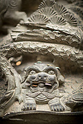 Close-up shot of multiple coins left in a dragon sculpture as a religious offering, Lingyin Buddhist temple, Hangzhou, Zhejiang Province, China