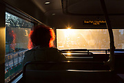 A lady passengers red hair glows in backlit winter sunlight through the front window while travelling on a bus along Piccadilly, on 20th January 2020, in London, England.