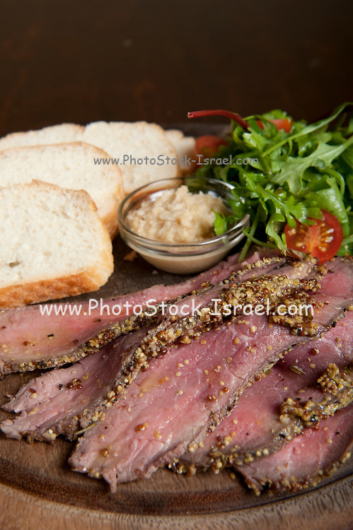 Roast Beef slices and white bread on a wooden platter