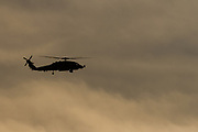 A silhouette of a US Navy Sikorsky SH-60R Seahawk helicopter with the the Maritime Strike Squadron 51 against a cloudy, dusk sky  near Naval Air Facility,, Atsugi airbase in Kanagawa, Japan. Thursday February 25th 2021