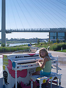 A girl plays a piano at the Omaha Plaza, with the Bob Kerrey Bridge in the background. Omaha, Nebraska.