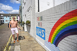 © Licensed to London News Pictures. 02/05/2020. Hammersmith, west London, UK. Nick Hamelin exercises outside his home under lockdown next to a new mural that has popped up overnight. The street art expressing support for the NHS during the COVID-19 crisis, is the creation of 12 year old Alex, helped by cousin Chelsea.  Photo credit: Guilhem Baker/LNP