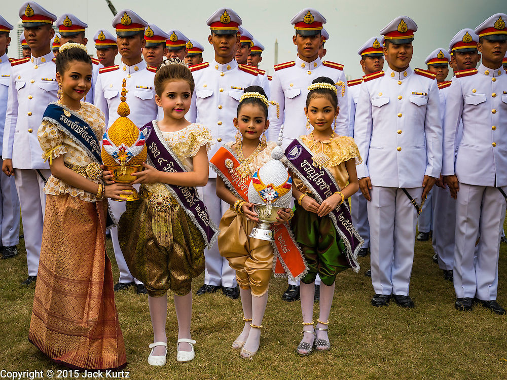 05 DECEMBER 2015 - BANGKOK, THAILAND: Children in traditional Thai dress prepare to make merit on the King's Birthday on Sanam Luang in Bangkok. Thais marked the 88th birthday of Bhumibol Adulyadej, the King of Thailand,  Saturday. The King was born on December 5, 1927, in Cambridge, Massachusetts. The family was in the United States because his father, Prince Mahidol, was studying Public Health at Harvard University. He has reigned since 1946 and is the world's currently the longest serving monarch in the world and the longest serving monarch in Thai history. Bhumibol, who is in poor health, is revered by the Thai people. His birthday is a national holiday and is also celebrated as Father's Day. He is currently hospitalized in Siriraj Hospital, recovering from a series of health setbacks.    PHOTO BY JACK KURTZ