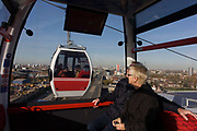 Passengers ride in a gondola on a journey over the River Thames on the Emirates Cable Car, from Royal Docks towards the Greenwich Peninsular. There are 34 gondolas, each with a maximum capacity of 10 passengers. The Emirates Air Line (also known as the Thames cable car) is a cable car link across the River Thames in London built with sponsorship from the airline Emirates. The service opened on 28 June 2012 and is operated by Transport for London. The service, announced in July 2010 and estimated to cost £60 million, comprises a 1-kilometre (0.62 mi) gondola line that crosses the Thames from the Greenwich Peninsula to the Royal Docks.