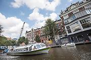In Amsterdam vaart een hop-on hop-off rondvaartboot door de Singelgracht.<br /> <br /> In Amsterdam a hop-on hop-off boat sails at the Singelgracht.