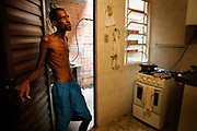 Flávio de Oliveira Pires, 34, leans against the door in his kitchen as he cooks lunch. He is a DOTS (Directly Observed Treatment, Short-course) patient at Gustavo Capanema Family Health Center in Elis Regina. He did not show up at the clinic to receive medicine, so the nurses went to his house to hand it in. He and his girlfriend broke up when their daughter was only one year old, and he could not live with her because of his health conditions.