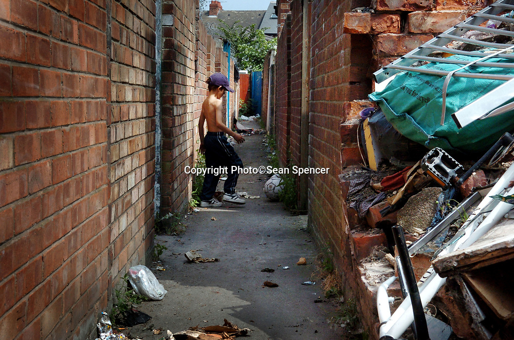 August 2006: A young boy plays football amongst glass and debris down an alley off Wellsted Street, Hull.<br /> Picture:Sean Spencer/Hull News & Pictures 01482 210267/07976 433960<br /> High resolution picture library at http://www.hullnews.co.uk<br /> ©Sean Spencer/Hull News & Pictures Ltd
