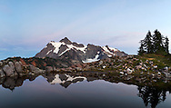 Mount Shuksan reflected in a tarn on Huntoon Point in the Mount Baker-Snoqualmie Forest, Washington State, USA.