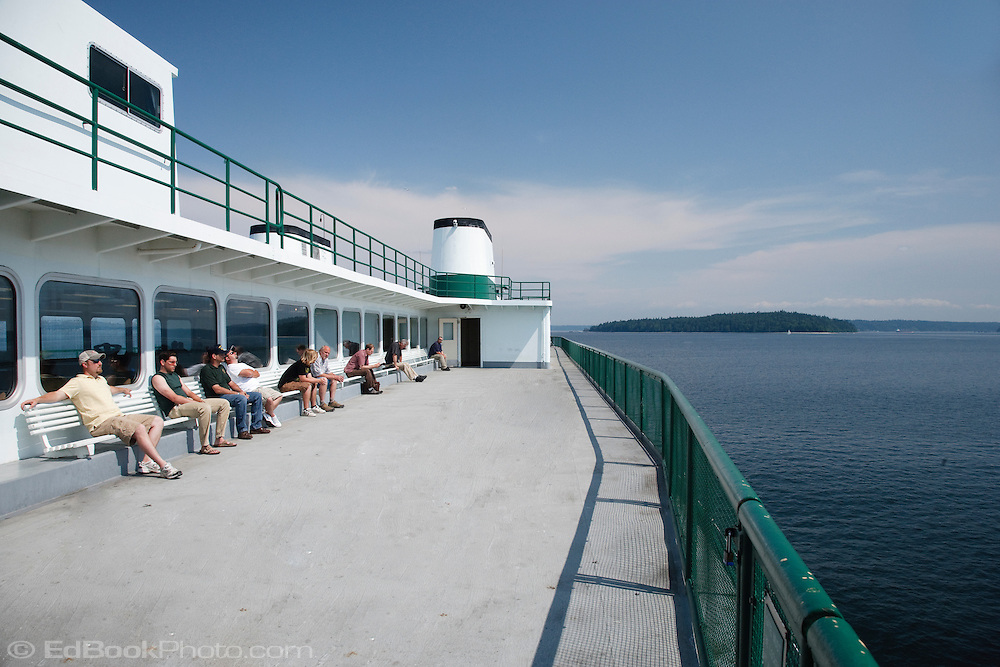 Commuters relax in the sun while crossing Puget Sound on a Washington State Ferry.